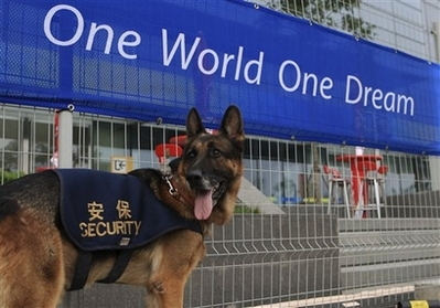 A police dog stands by under a banner of the Beijing 2008 Olympics slogan 'One World One Dream' in Beijing, Thursday, Aug. 7, 2008, a day before the Summer Games' opening ceremony. (AP Photo/Robert F. Bukaty)