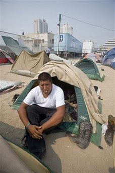 Mack Martinez, 19, of Cedar Rapids, Iowa, smokes in front of his tent at the tent city that sprung up next to the homeless shelter in downtown Reno, Nev., Wednesday, June 25, 2008. Martinez, who says he has never been more than two weeks without work, had a run of bad luck in Las Vegas before moving to Reno to look for work. [Agencies]