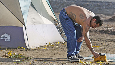 Resident of a tent city sweeps up outside his home in Ontario